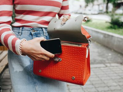 Woman opening purse to put a phone in the bag