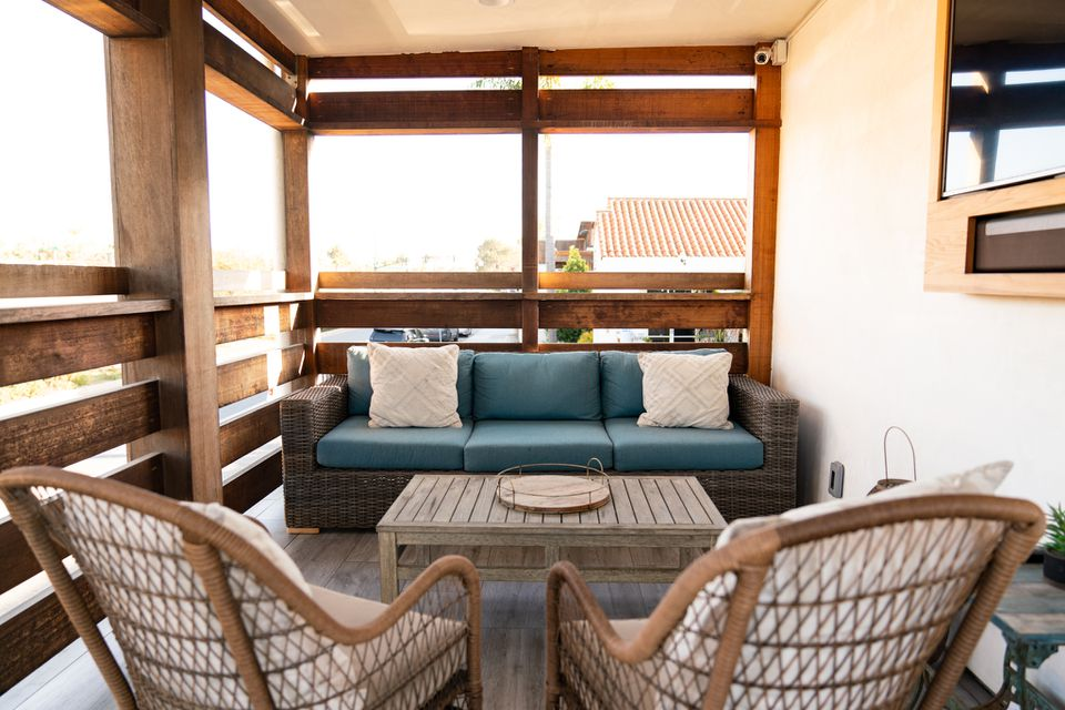 Outdoor deck with wooden beams and wicker and wooden furniture