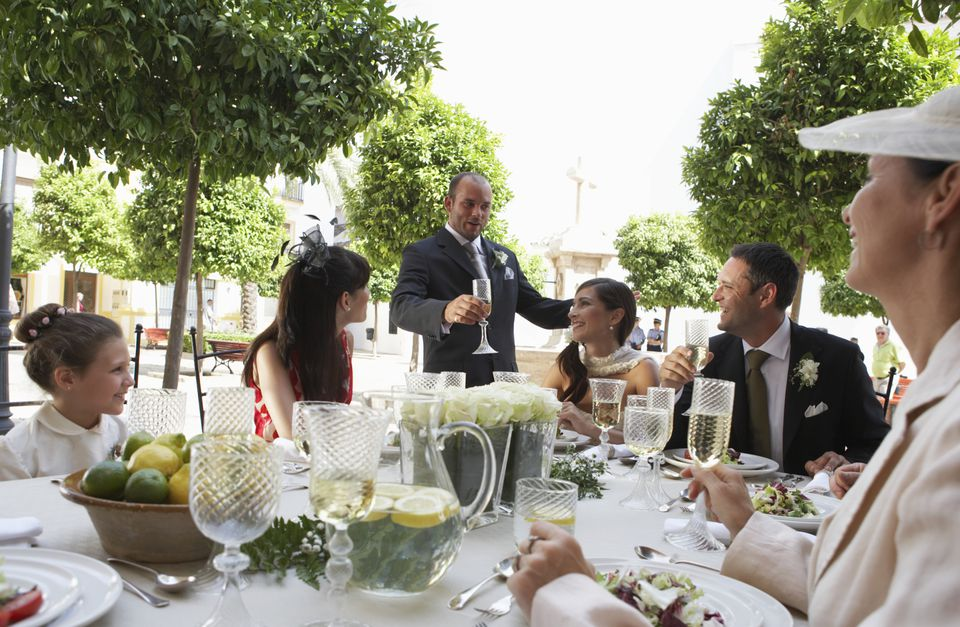 Man standing to toast bride and groom at outdoor dinner table