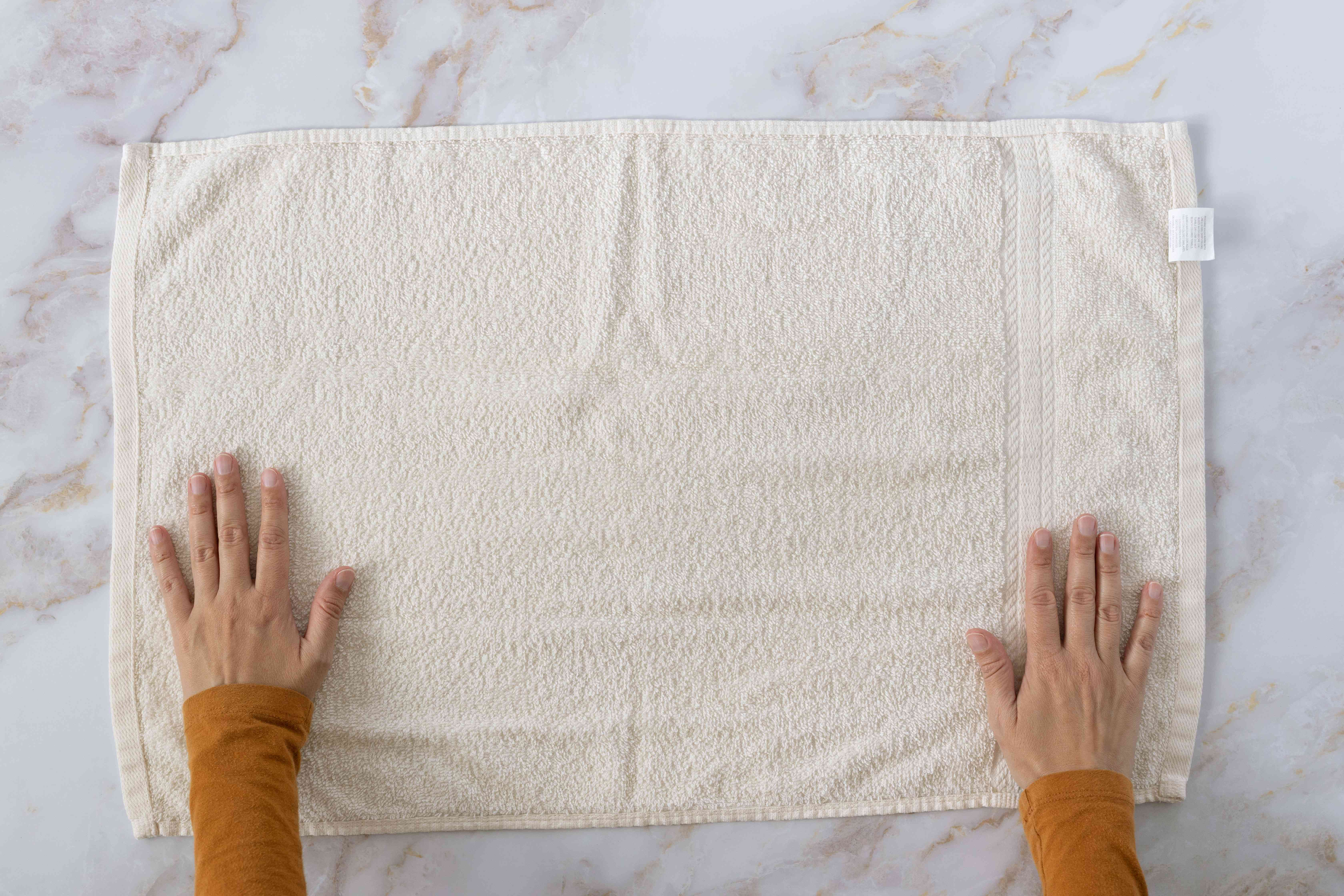 Large cream towel laid flat on marbles surface