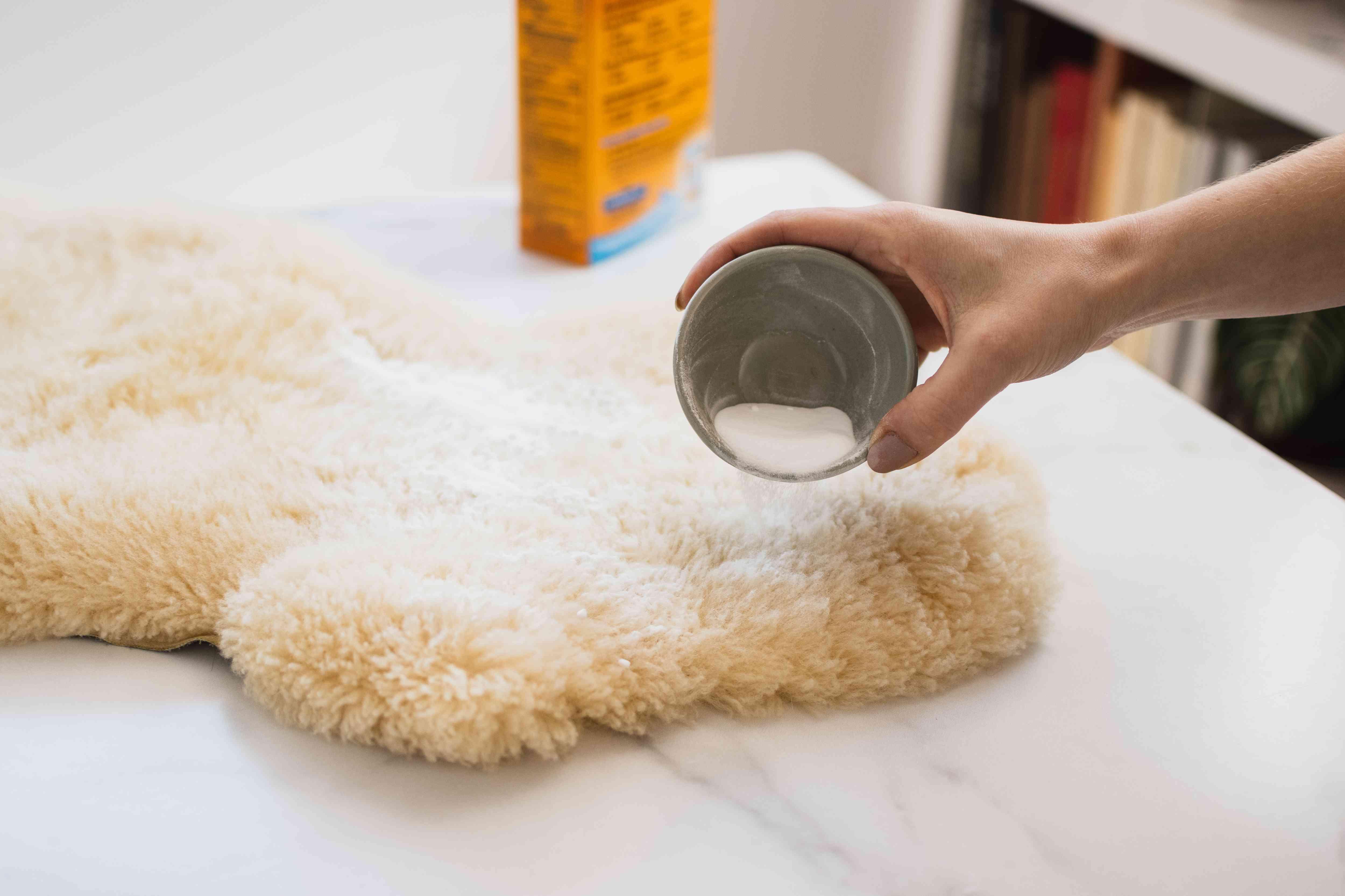 Baking soda poured on sheepskin rug to remove odors