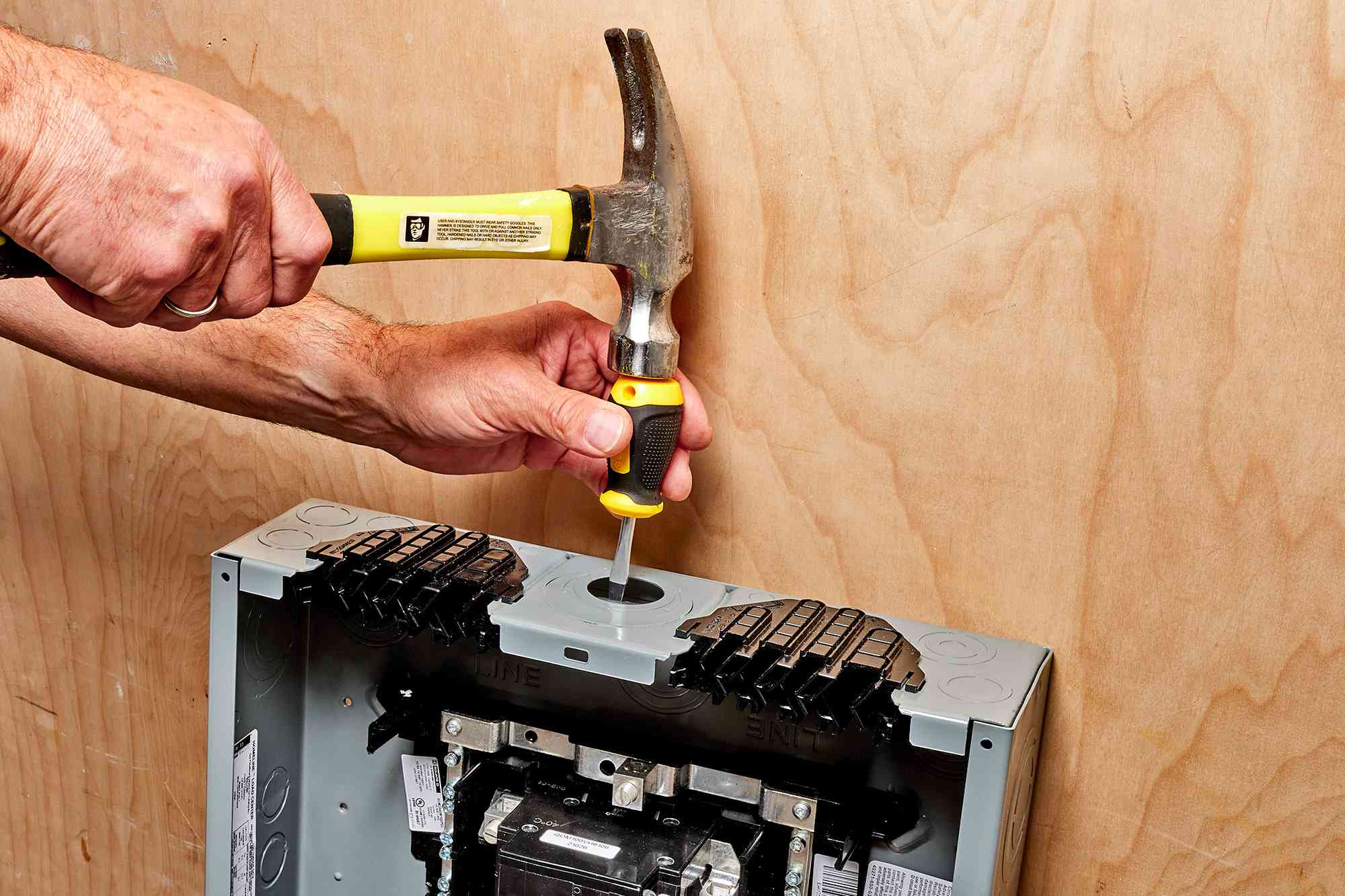 Hammer tapping opening metal knockout on top of electric panel with screwdriver