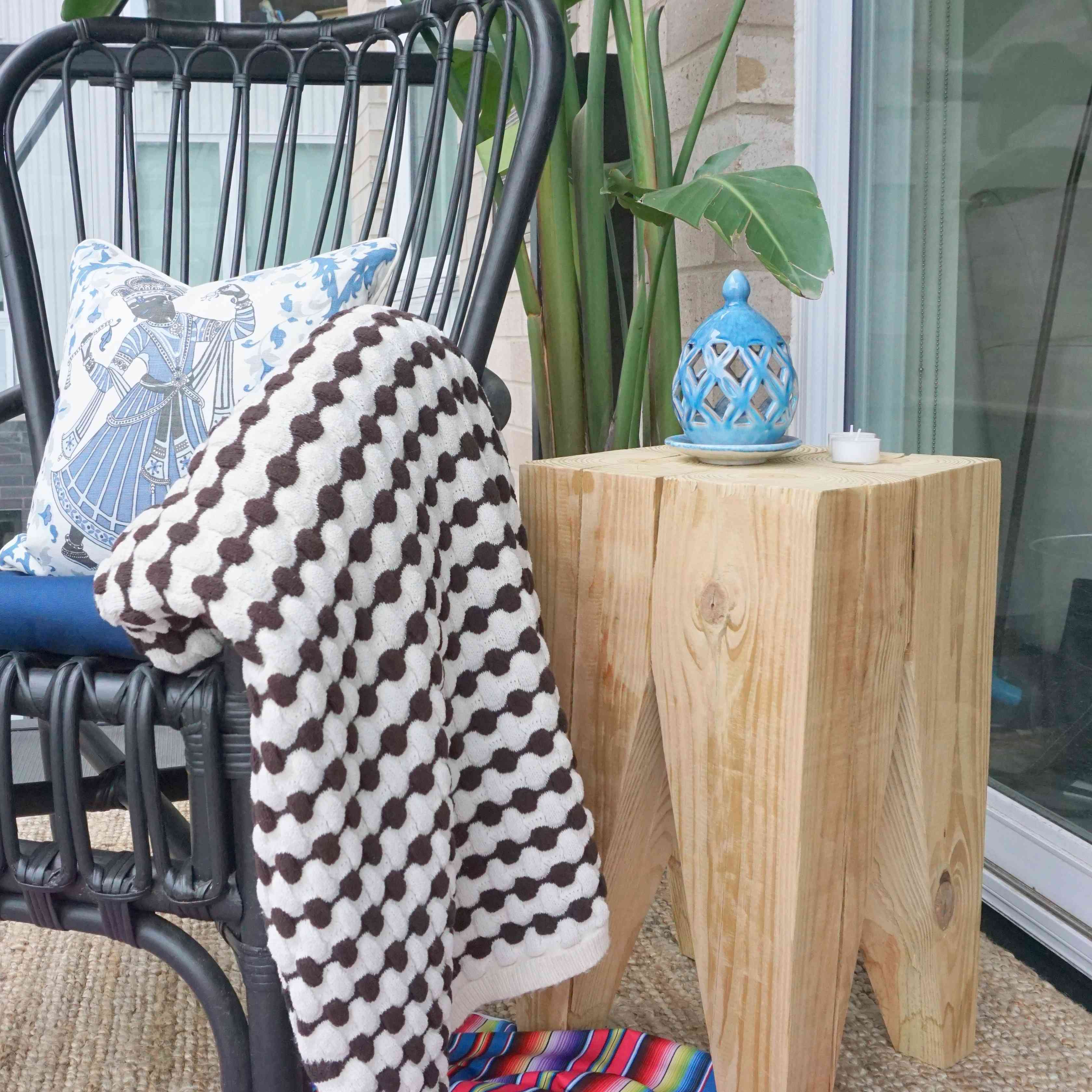 A wooden side table on a porch