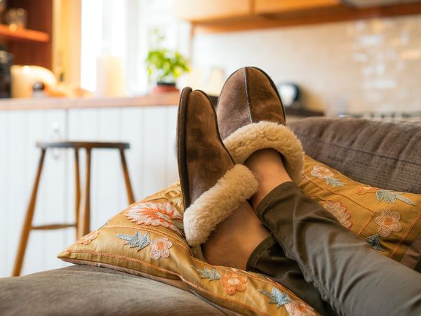 Woman wearing brown shearling slippers with feet up on sofa
