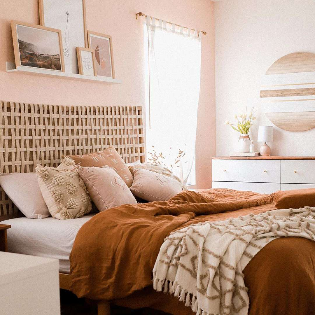 Bedroom with pink walls and orange bedspread