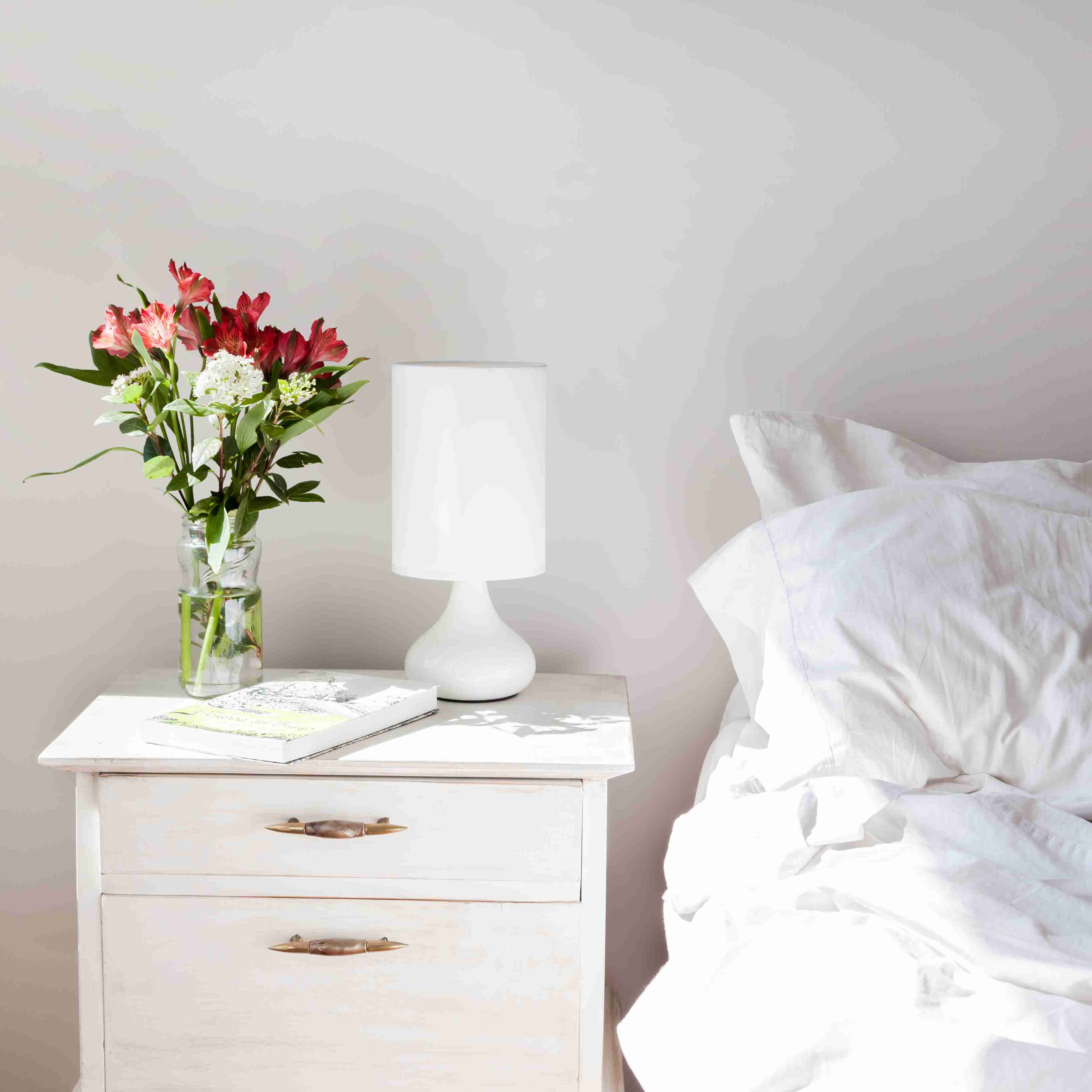 white bedroom with flowers on the bedside table