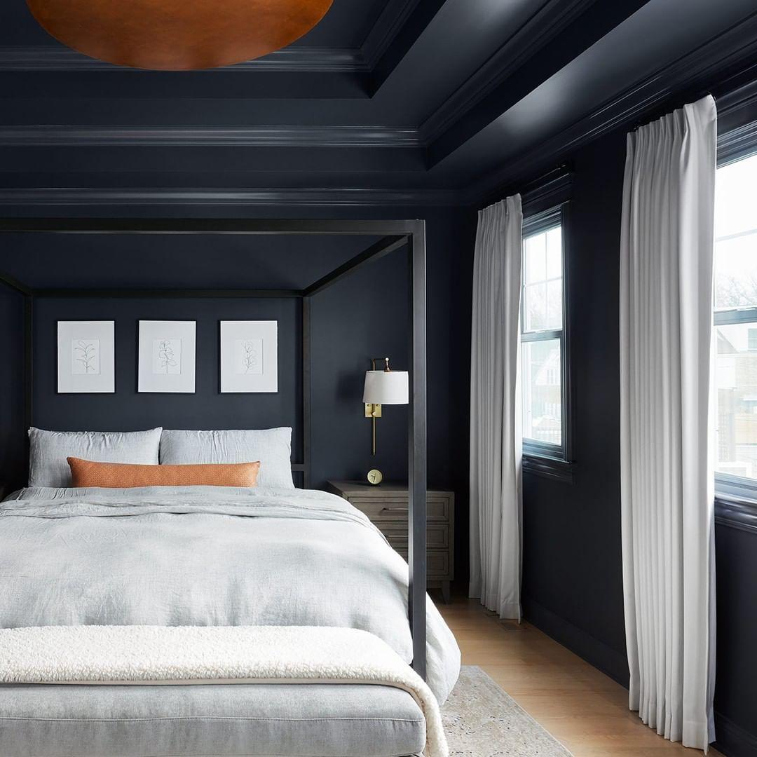 Habitación con paredes negras y ropa de cama gris