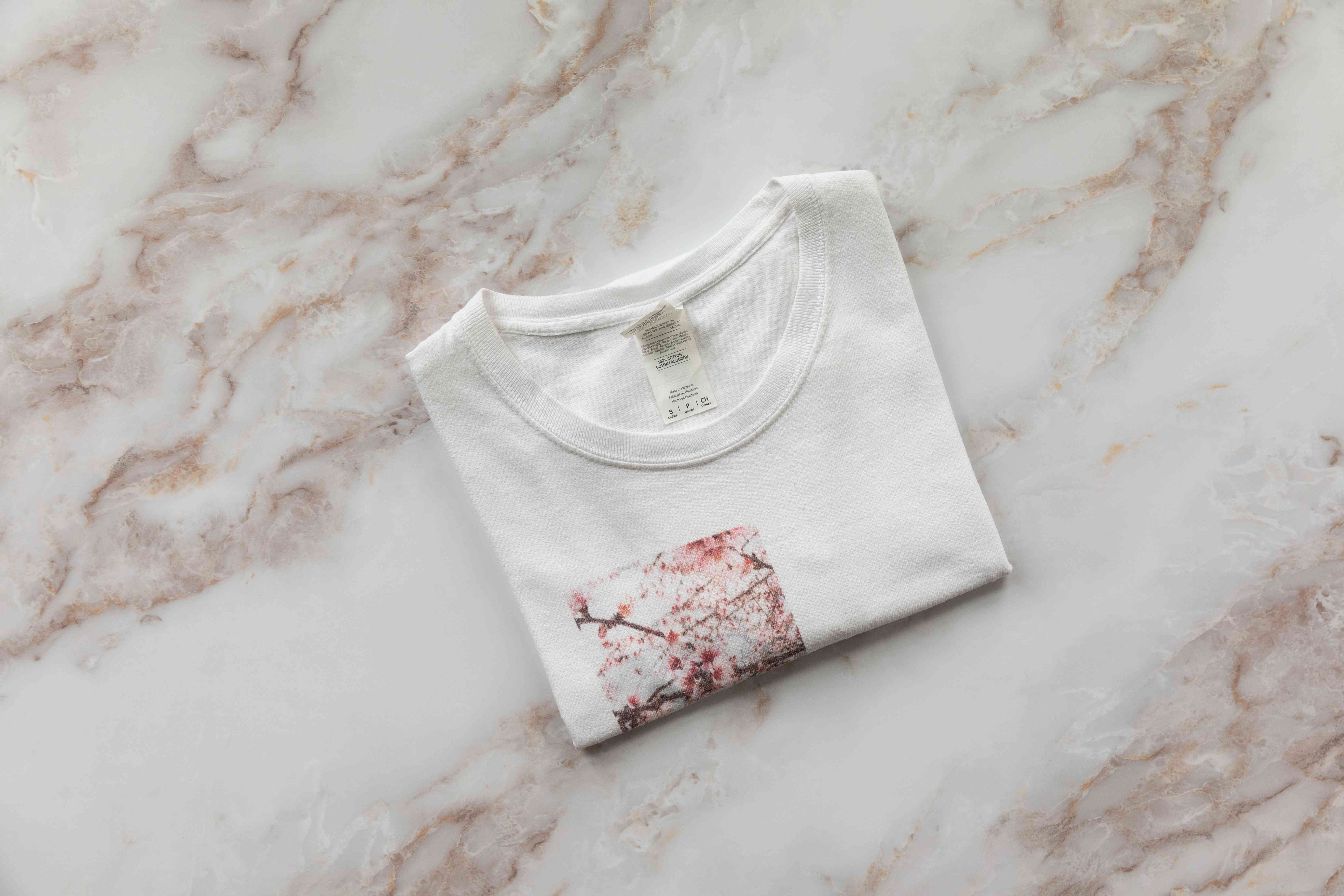 White t-shirt with red printed image folded neatly on white marbled surface
