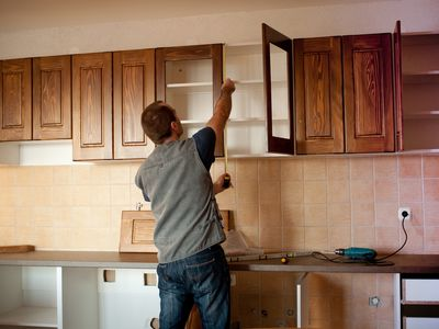 Man installing kitchen cabinets