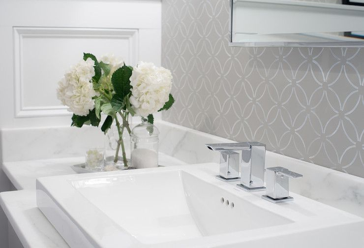 Grey and white bathroom with modern sink and a vase of flowers.