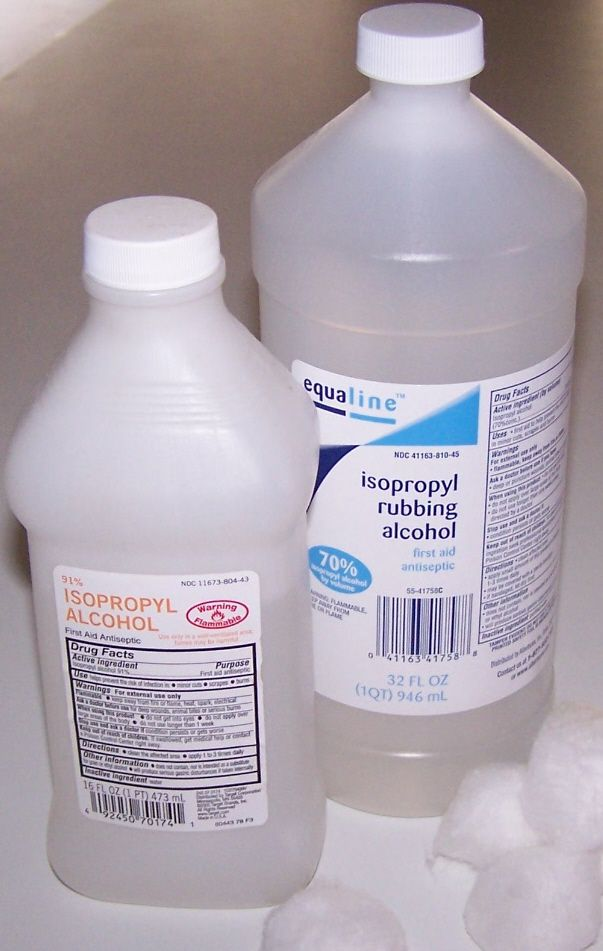 Two bottles of isopropyl rubbing alcohol in a cabinet.