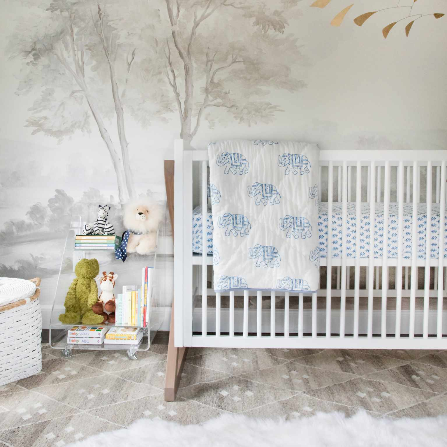 a gray tree-themed wallpaper mural sets the tone for this soft white nursery
