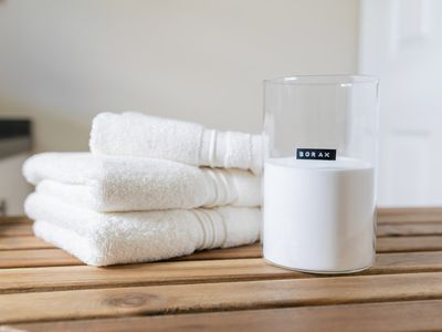 container of borax next to a stack of towels