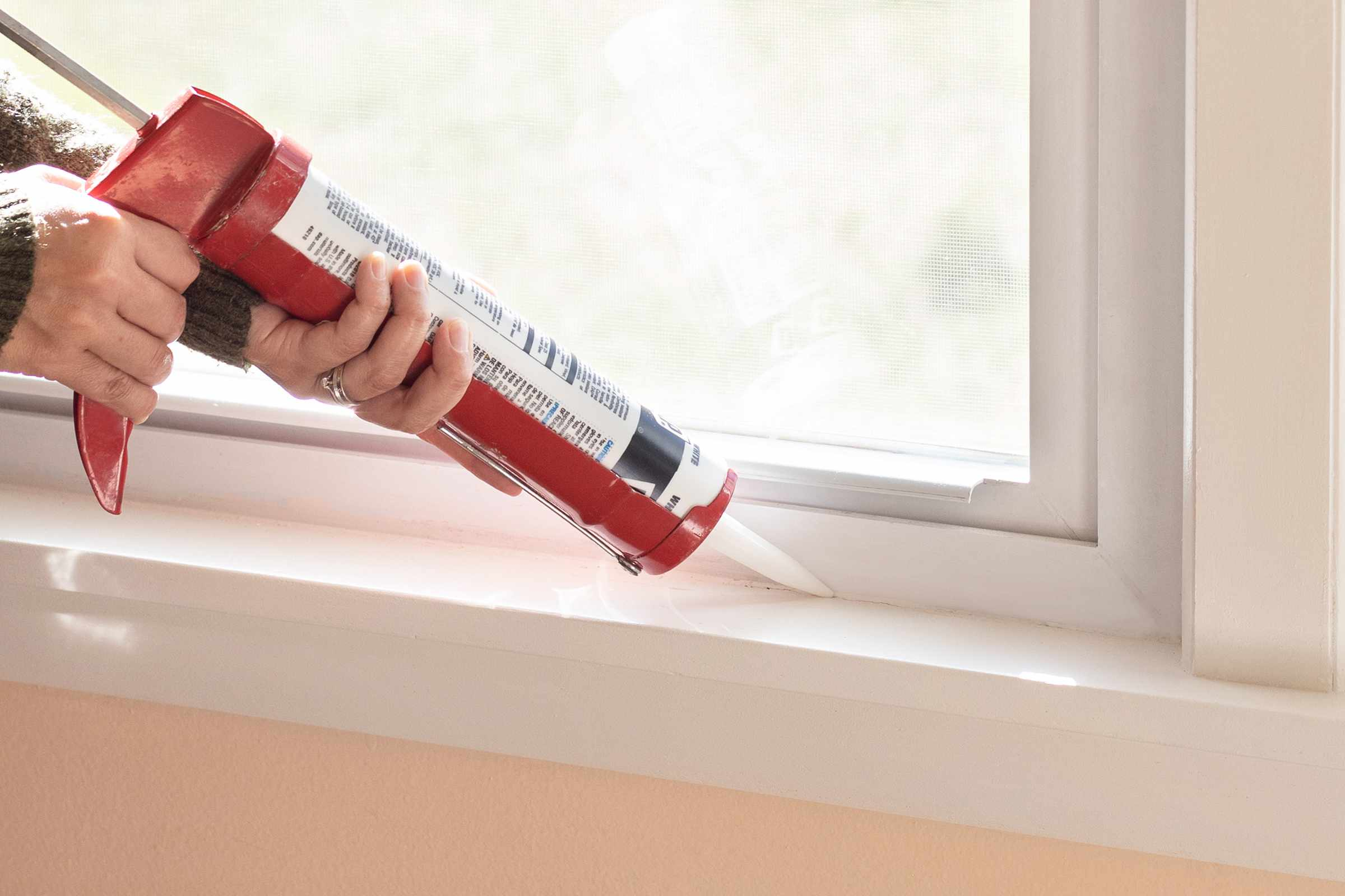 Interior crack near window being sealed with caulk gun