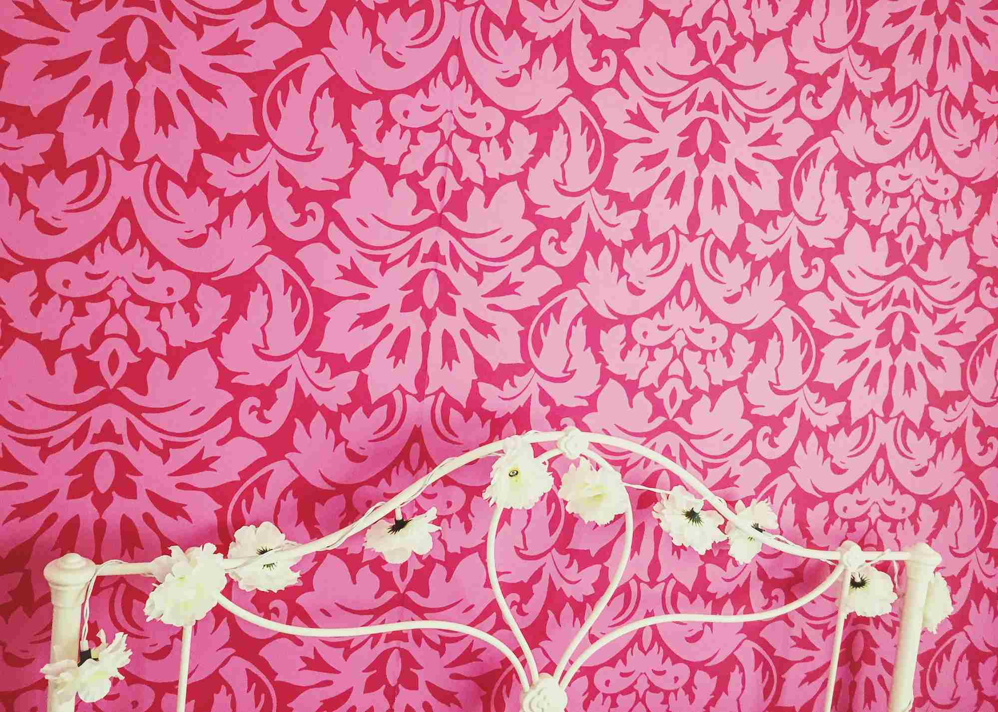 White metal bed headboard pink wallpaper