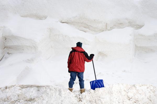 Man with shovel staring at big pile of snow