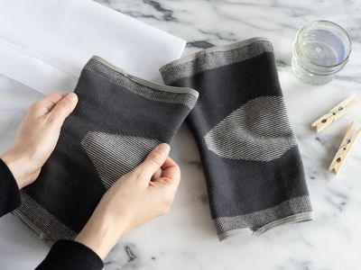 Black and gray compression garments held in hand next to glass of water and clothing pins