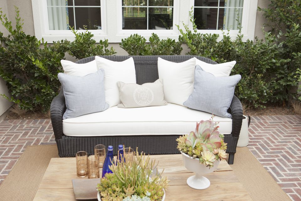Wicker couch with cushions on brick flooring on a patio