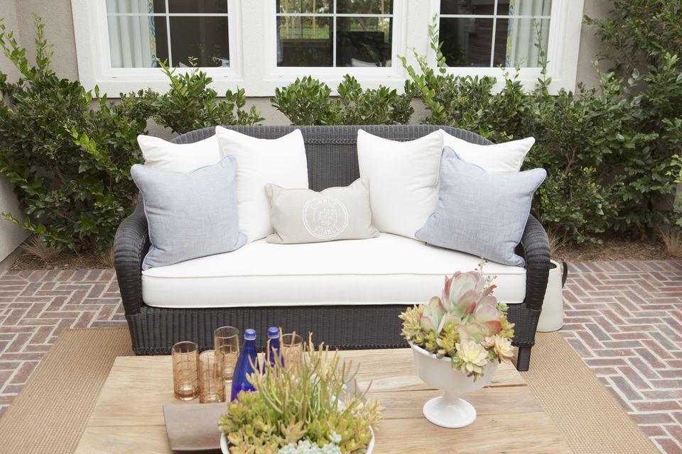 Sofá de mimbre con cojines en pisos de ladrillo en un patio