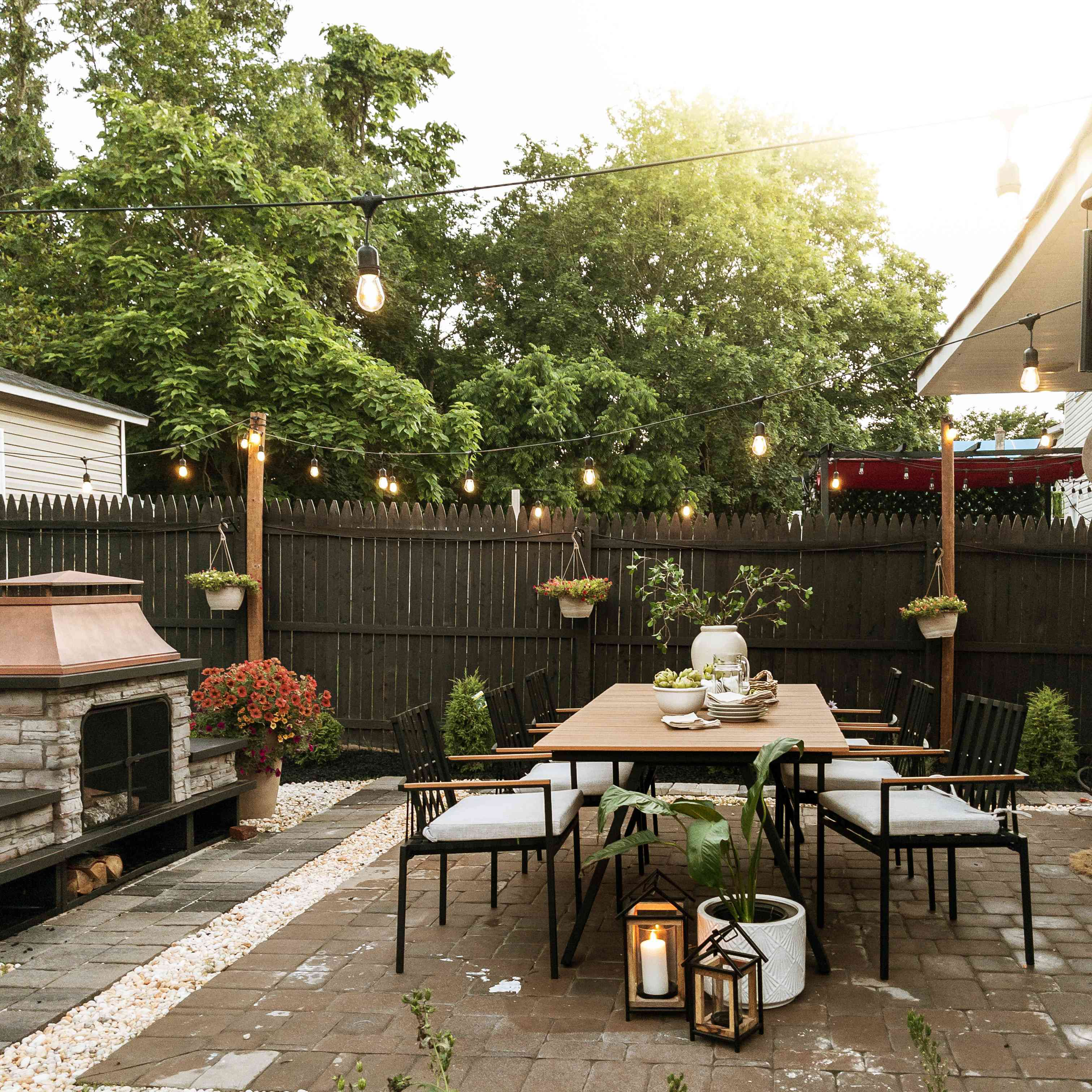 the patio has a huge dining table and a fire pit, along with string lights and lanterns and plants