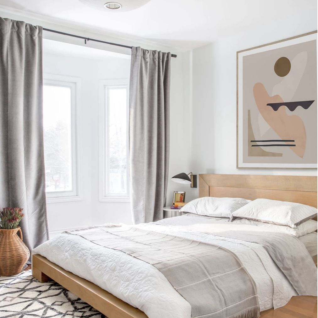 bedroom with pattern rug and abstract artwork on the wall