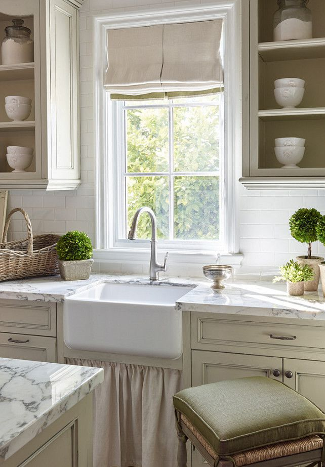 French country kitchen with open cabinets and window overlooking the sink.