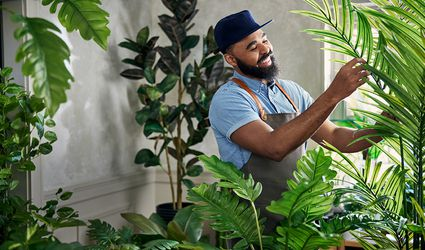 Hilton Cater surrounding by plants in his home.