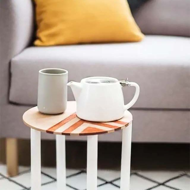 A side table with a teapot and cup on it