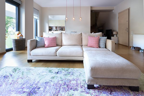Living room with a three seater sofa with chase and four little pillows.
