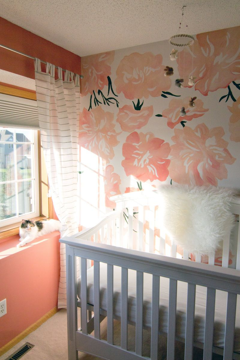 Coral and white nursery with bold floral accent wall.