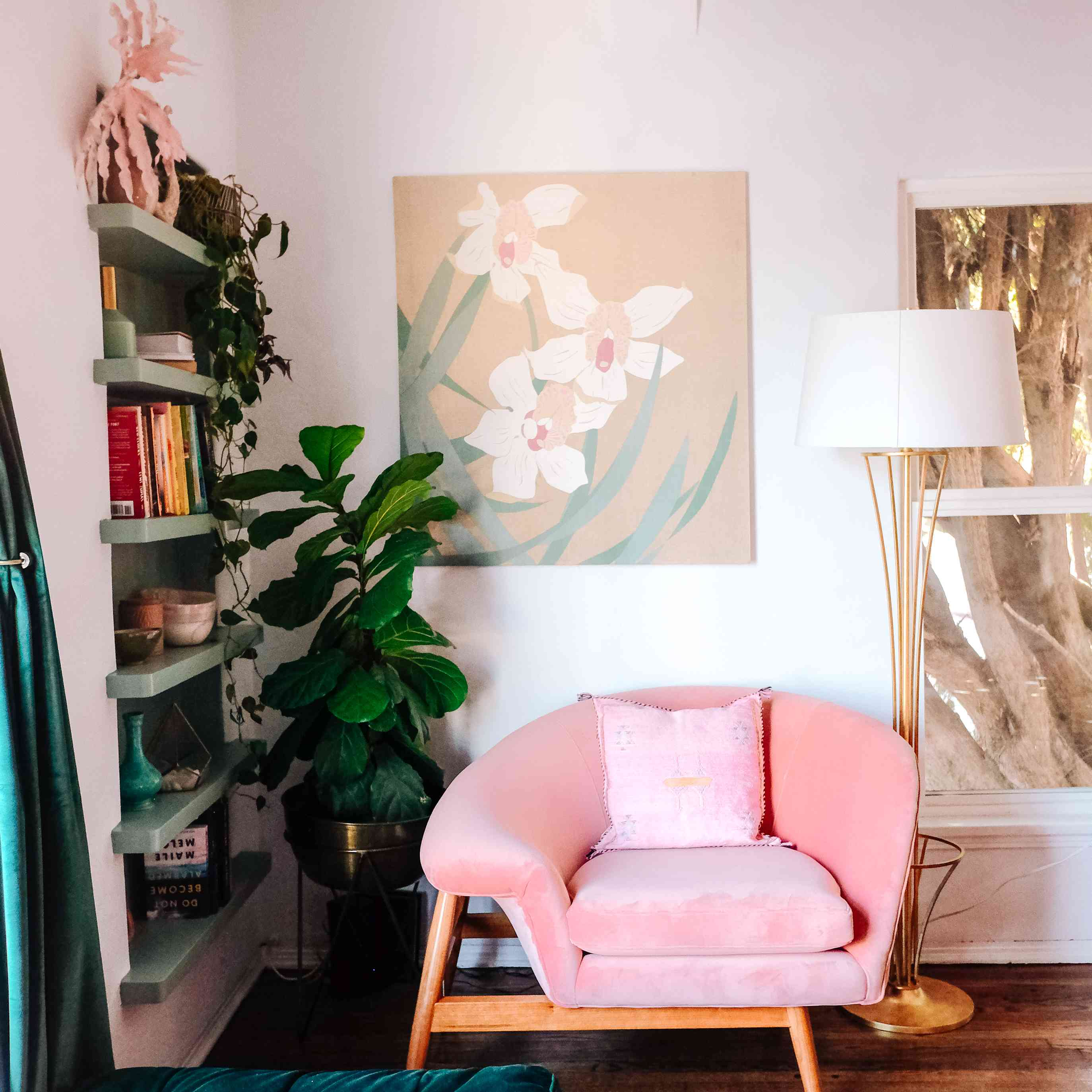cozy reading corner with pink chair, floating bookshelf built into wall, artwork and plant