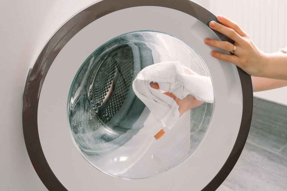 person wiping the inside of a washer