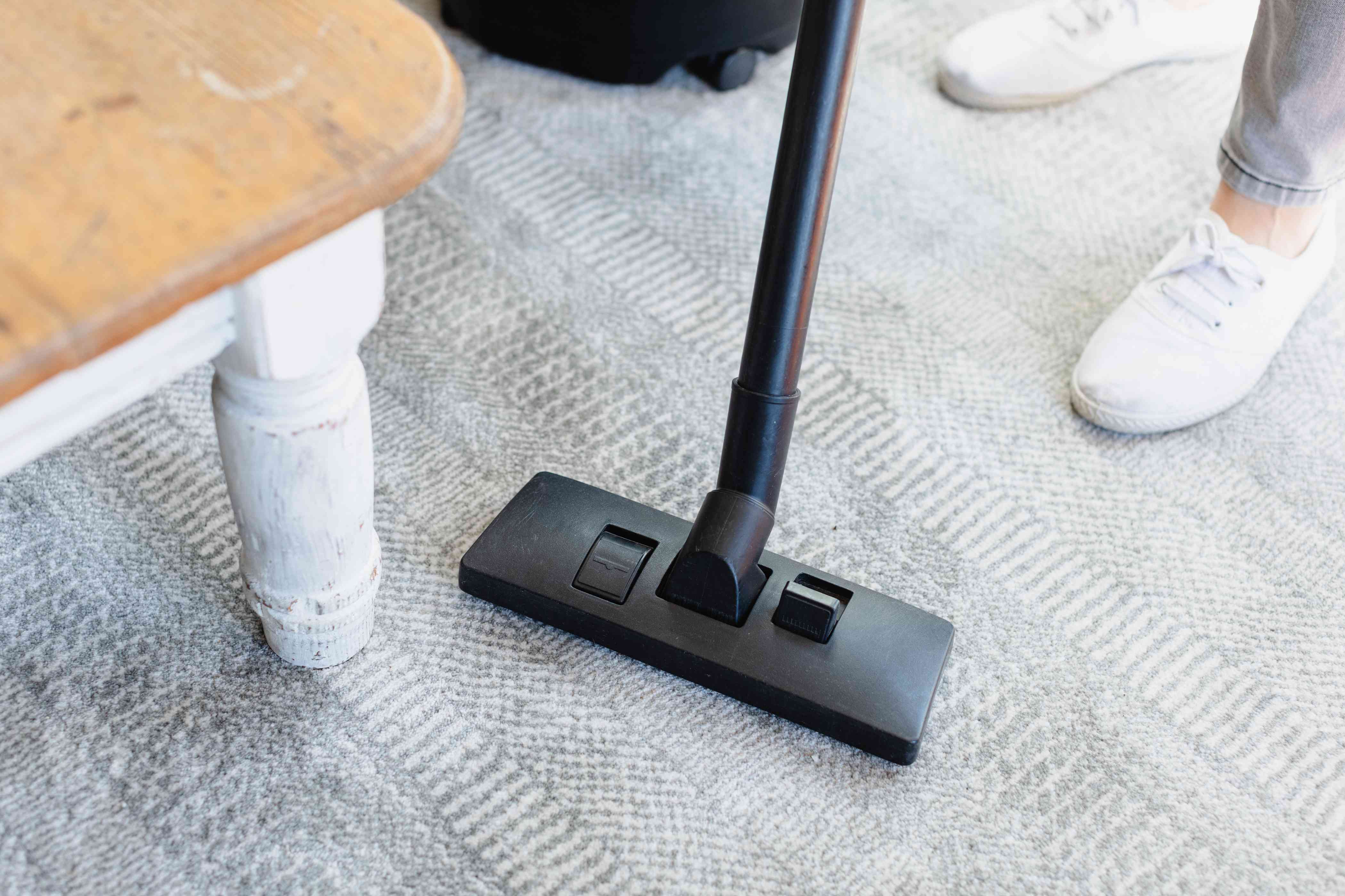 Upright vacuum cleaner cleaning carpet around table leg