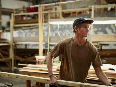 a man holding a long piece of lumber