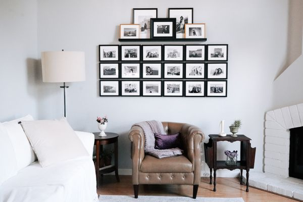 Gallery wall of photos in living room with white couch and brown chair