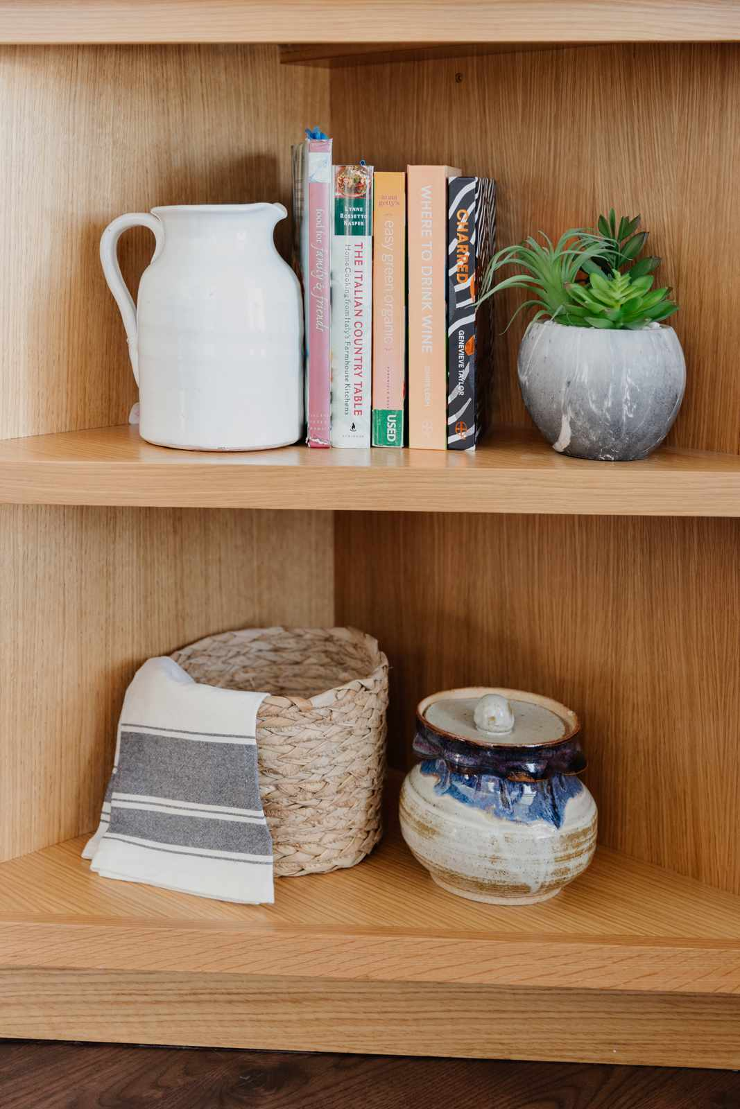 wooden corner shelf with cookbooks, plant, and other small decor items