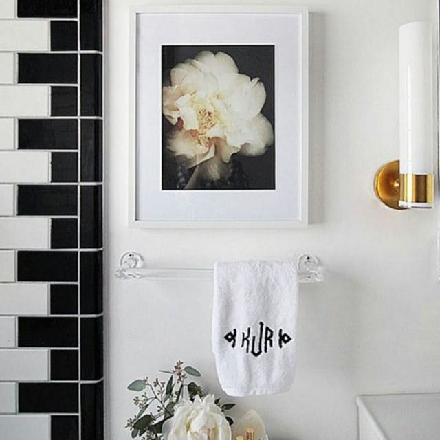 Black and white bathroom with white flowers and gold accents