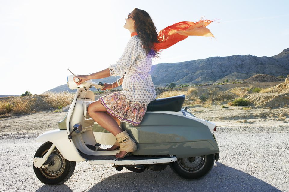 Woman on a vespa with her scarf in the air