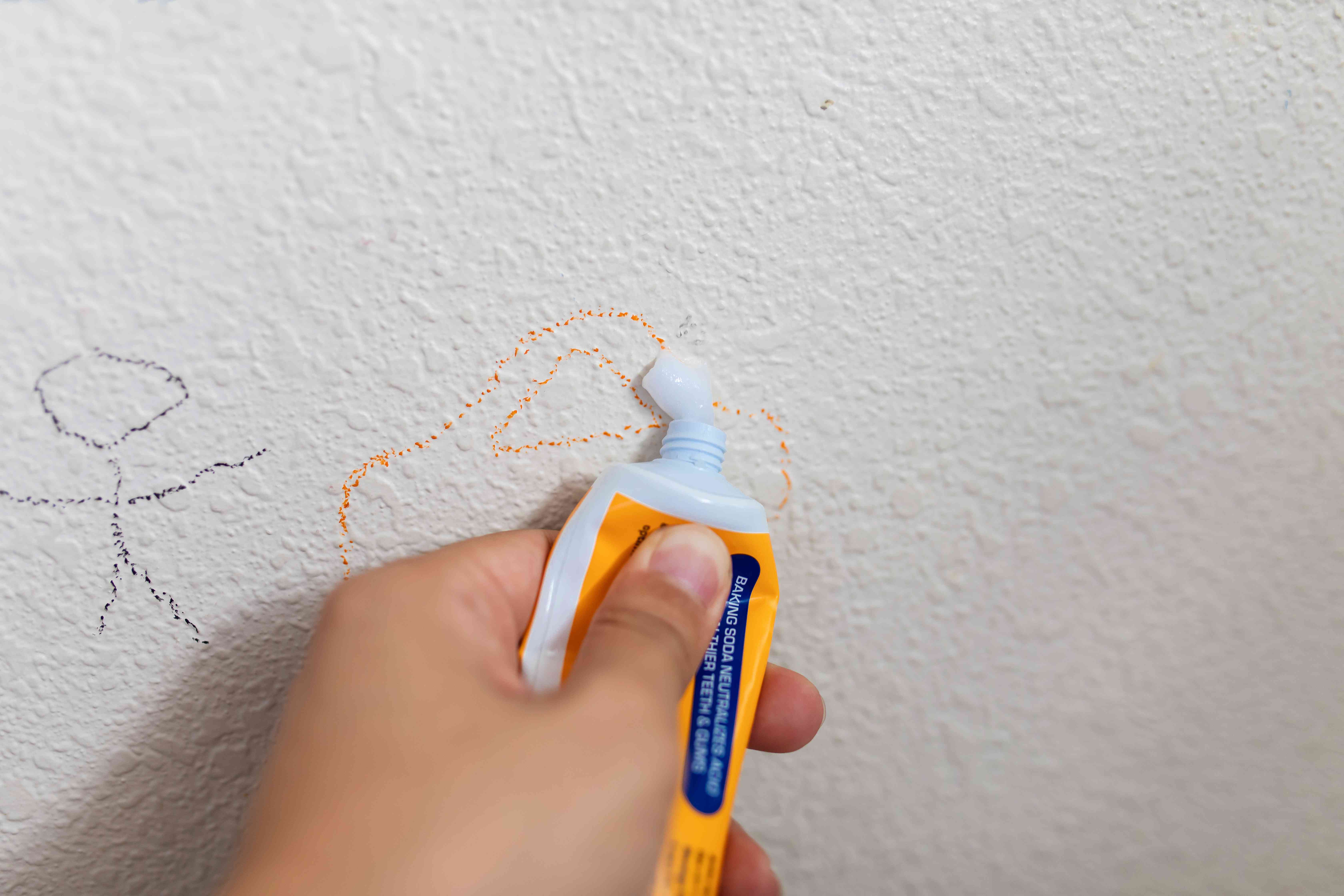 person applying toothpaste to a crayon stain