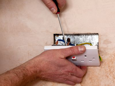 cutting outlet holes in drywall to install an electrical box