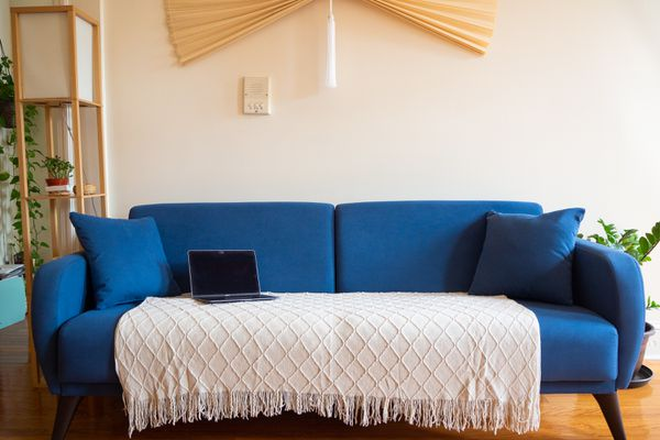 Blue sofa bought online with white patterned throw blanket with light colored decor items and houseplants