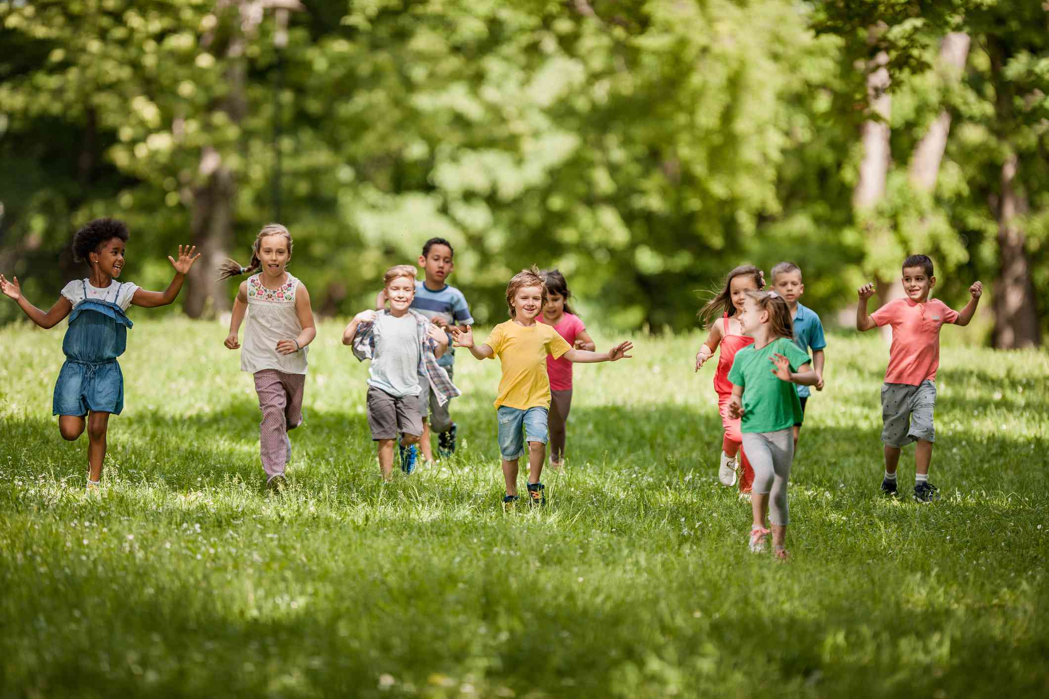 Carefree children having fun while running in spring day at the park.