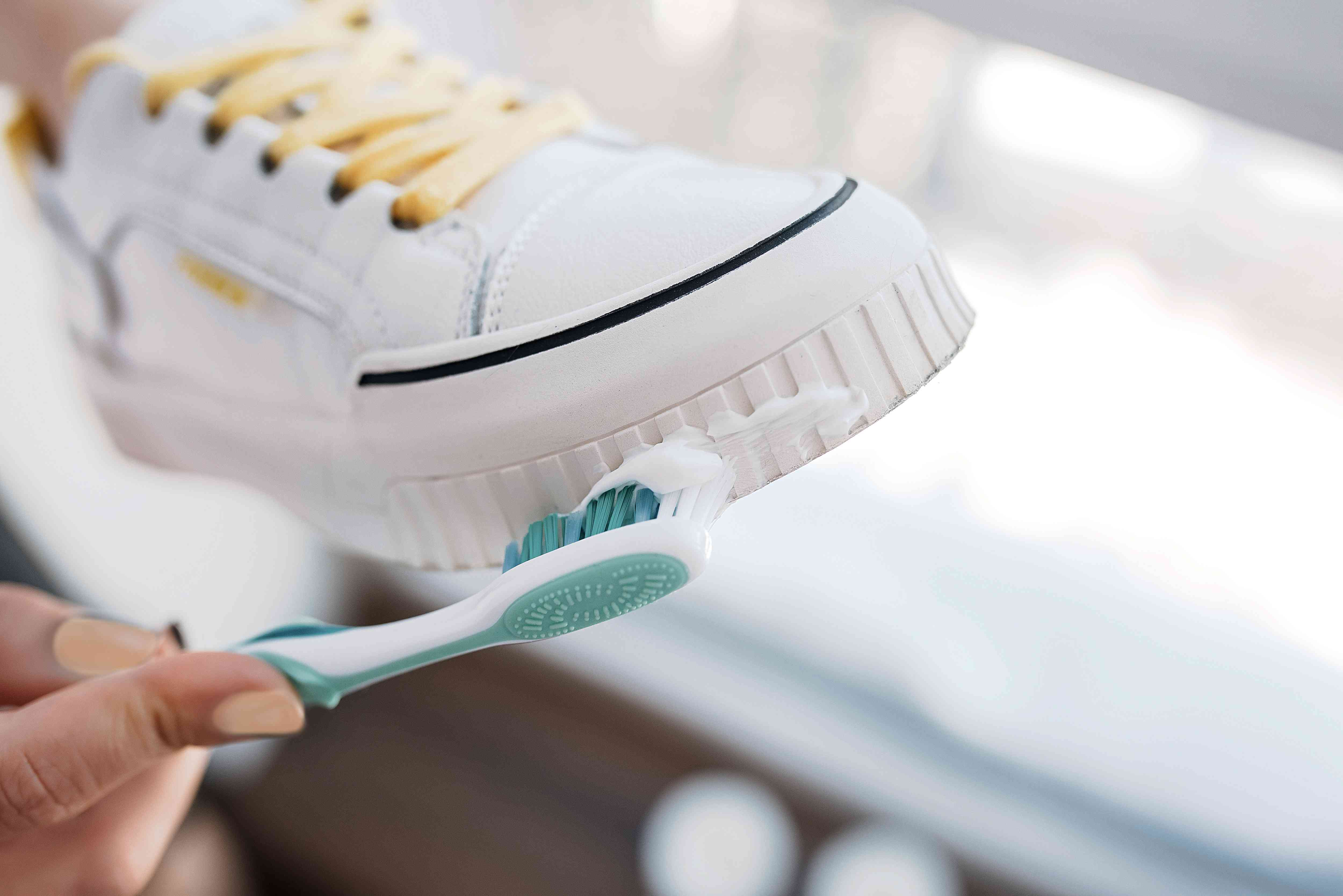 using toothpaste to clean the sole of a sneaker