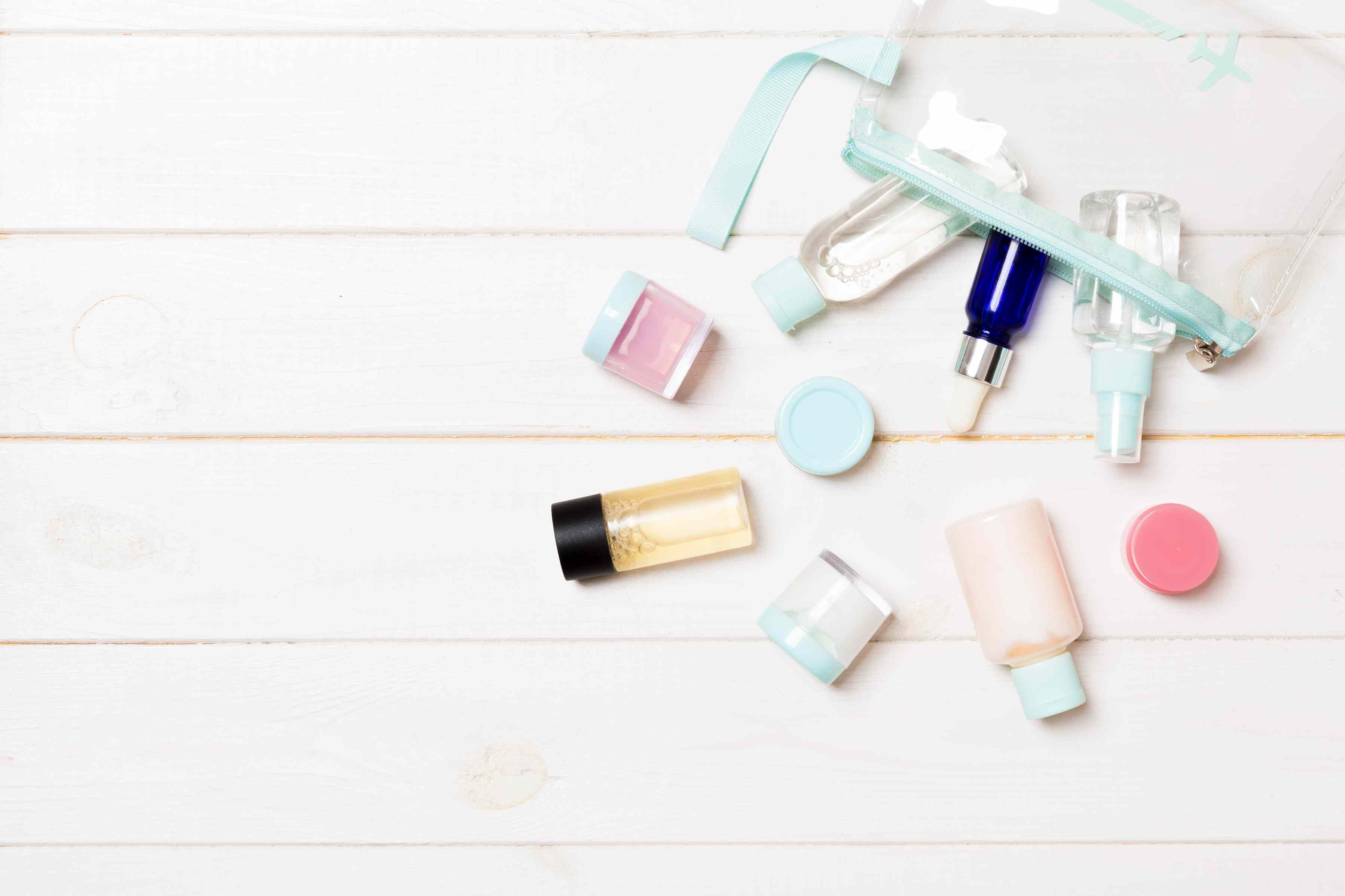 Set of travel size cosmetic bottles on white wooden background. Flat lay of cream jars. Top view of bodycare style concept