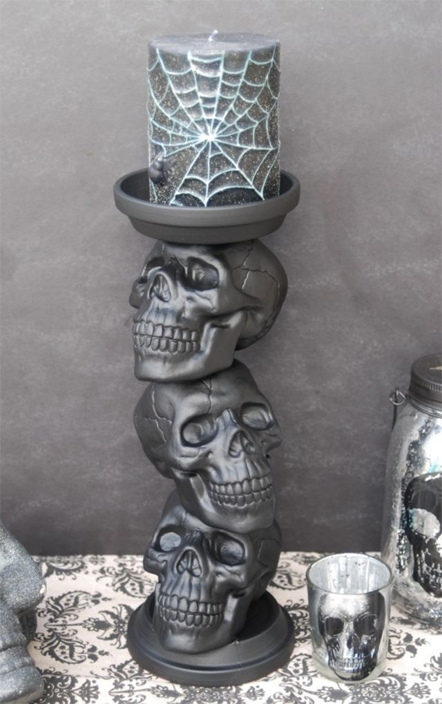 A gray candle holder made of skulls