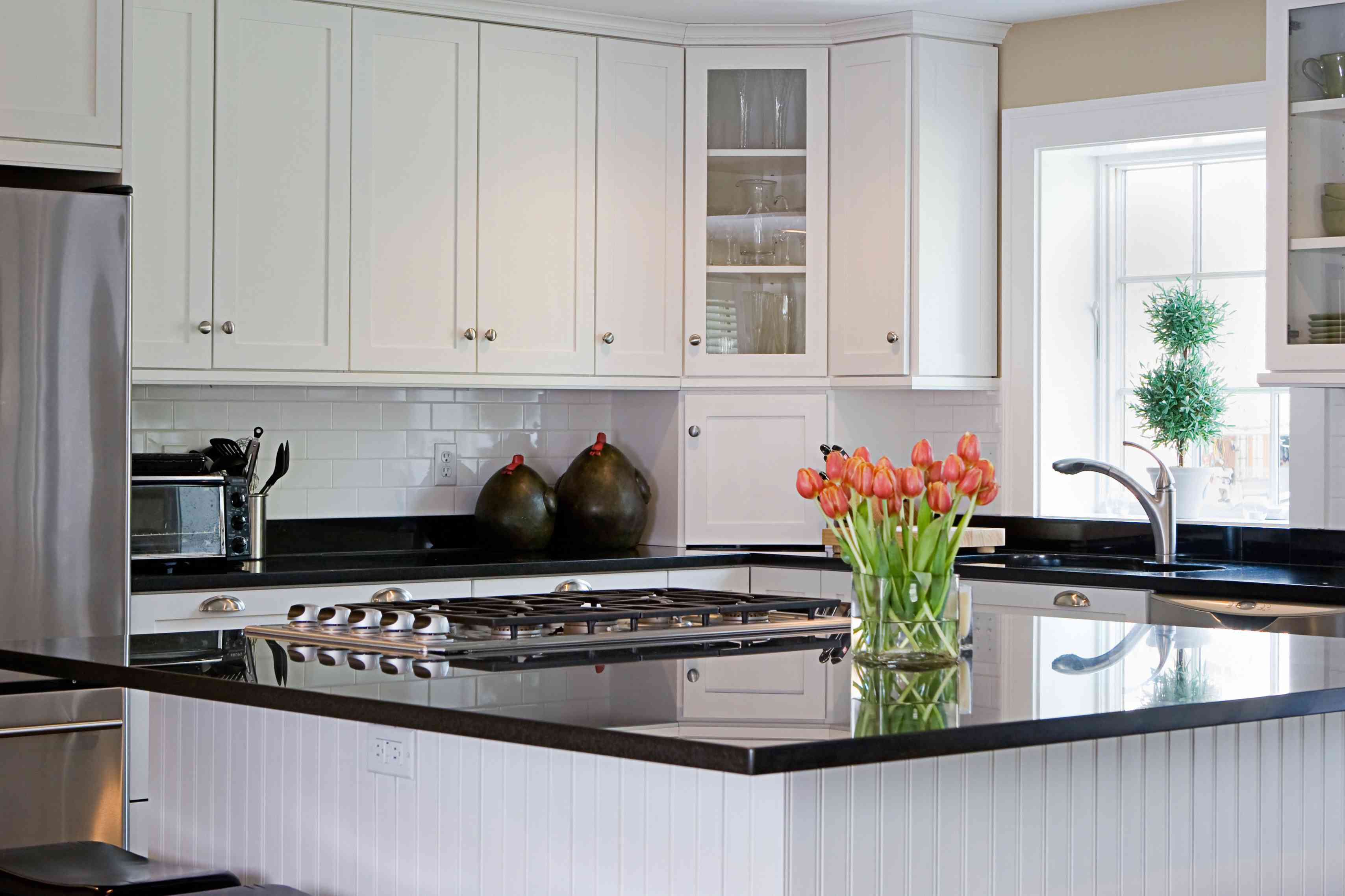 Well-lit kitchen with black granite countertop