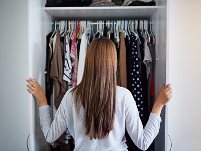 woman looking at clothes in wardrobe