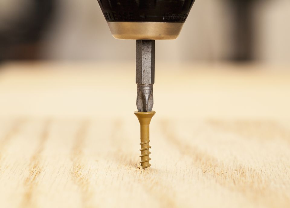 Brown screw being driven into wood by phillips bit in power drill