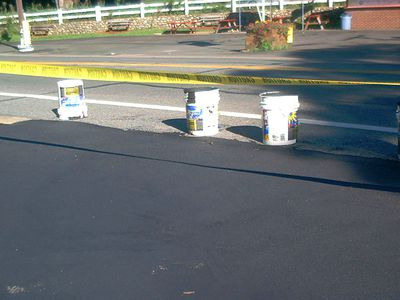 Barricade tape for a newly sealed driveway to keep cars away.