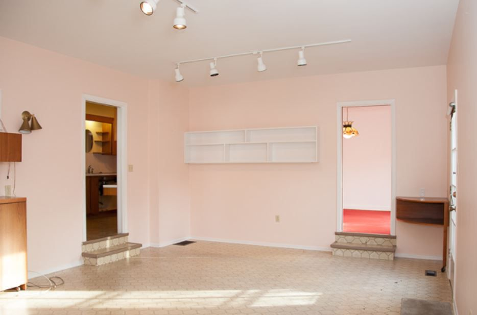 Empty dining room with light peach walls and white track lighting.